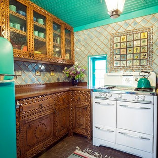 Mid-sized southwestern kitchen ideas - Inspiration for a mid-sized southwestern u-shaped brick floor kitchen remodel in Albuquerque with a double-bowl sink, medium tone wood cabinets, multicolored backsplash, no island, wood countertops, terra-cotta backsplash and colored appliances