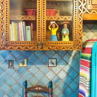 アルバカーキの中くらいのサンタフェスタイルのおしゃれなコの字型キッチン (ダブルシンク、中間色木目調キャビネット、マルチカラーのキッチンパネル、白い調理設備、アイランドなし) の写真
