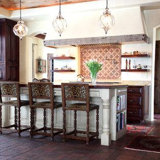 Foto de cocina de galera, mediterránea, con armarios con paneles con relieve, puertas de armario de madera en tonos medios y suelo de ladrillo
