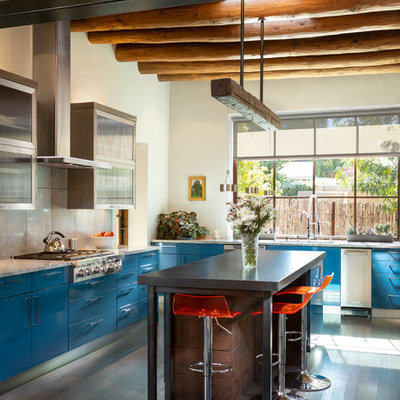 Large eclectic l-shaped dark wood floor and brown floor kitchen photo in Albuquerque with flat-panel cabinets, blue cabinets, stainless steel appliances, an island, white countertops, gray backsplash and cement tile backsplash