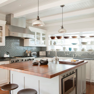 This is an example of a beach style kitchen in Los Angeles with glass-front cabinets, white cabinets, wood benchtops, grey splashback, subway tile splashback and stainless steel appliances.