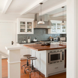 Inspiration for a beach style kitchen remodel in Los Angeles with glass-front cabinets, white cabinets, wood countertops, blue backsplash, subway tile backsplash and stainless steel appliances