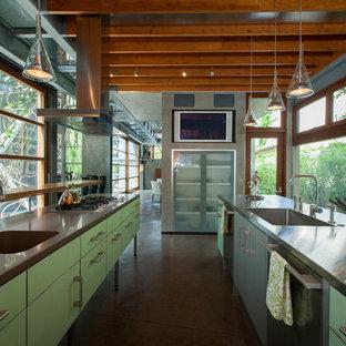 Zweizeilige Industrial Küche mit integriertem Waschbecken, flächenbündigen Schrankfronten, grünen Schränken, Edelstahl-Arbeitsplatte, Küchengeräten aus Edelstahl, Betonboden, Kücheninsel und grauem Boden in Los Angeles