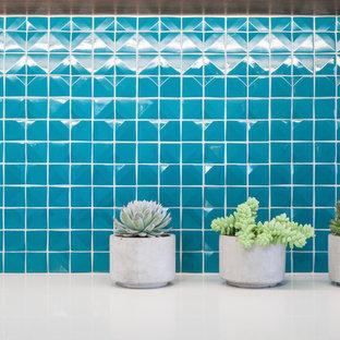 ロサンゼルスの中サイズのミッドセンチュリースタイルのおしゃれなキッチン (アンダーカウンターシンク、フラットパネル扉のキャビネット、中間色木目調キャビネット、クオーツストーンカウンター、緑のキッチンパネル、ガラスタイルのキッチンパネル、シルバーの調理設備の) の写真