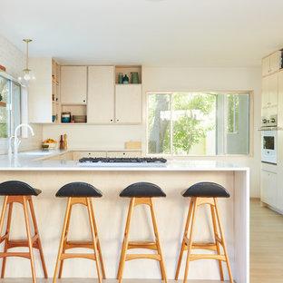 Inredning av ett 50 tals u-kök, med släta luckor, skåp i ljust trä, vitt stänkskydd, stänkskydd i keramik, integrerade vitvaror, en integrerad diskho, ljust trägolv, en halv köksö och beiget golv