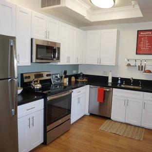 Offene, Kleine Moderne Küche ohne Insel in L-Form mit Waschbecken, Schrankfronten mit vertiefter Füllung, weißen Schränken, Quarzwerkstein-Arbeitsplatte, Küchengeräten aus Edelstahl und Vinylboden in Los Angeles