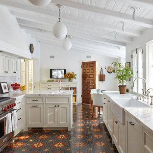 ロサンゼルスの地中海スタイルのおしゃれなキッチン (エプロンフロントシンク、シェーカースタイル扉のキャビネット、ベージュのキャビネット、シルバーの調理設備、セラミックタイルの床、赤い床、白いキッチンカウンター、サブウェイタイルのキッチンパネル) の写真