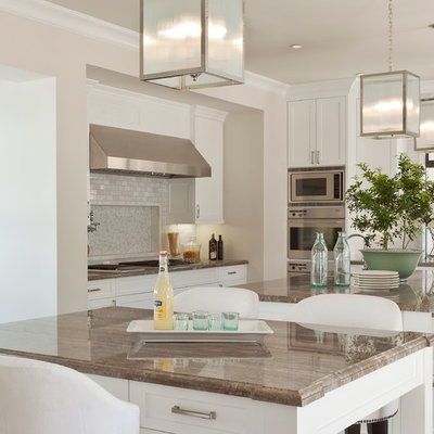 Example of a tuscan eat-in kitchen design in Orange County with white cabinets, gray backsplash, subway tile backsplash and stainless steel appliances