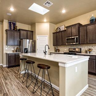 Esempio di una cucina classica con lavello sottopiano, ante in stile shaker, ante marroni, paraspruzzi beige, elettrodomestici in acciaio inossidabile, pavimento in legno verniciato, isola, pavimento multicolore e top bianco