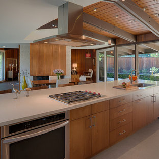 Large midcentury single-wall eat-in kitchen in San Francisco with an undermount sink, flat-panel cabinets, medium wood cabinets, quartz benchtops, vinyl floors, stainless steel appliances, with island and beige floor.