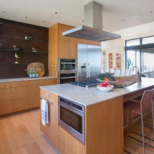 サンタバーバラの大きいサンタフェスタイルのおしゃれなキッチン (フラットパネル扉のキャビネット、中間色木目調キャビネット、シルバーの調理設備の、無垢フローリング、グレーのキッチンカウンター、アンダーカウンターシンク、大理石カウンター、茶色いキッチンパネル、茶色い床) の写真