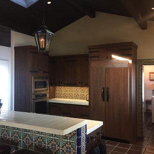 サンタバーバラの中サイズの地中海スタイルのおしゃれなキッチン (ドロップインシンク、レイズドパネル扉のキャビネット、濃色木目調キャビネット、タイルカウンター、マルチカラーのキッチンパネル、セラミックタイルのキッチンパネル、パネルと同色の調理設備、テラコッタタイルの床、黒い床、白いキッチンカウンター) の写真