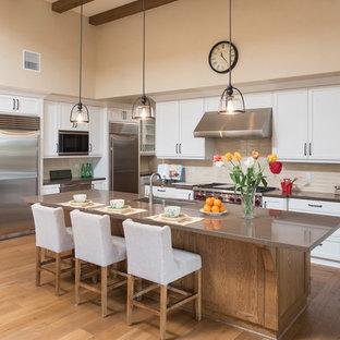 サンディエゴのサンタフェスタイルのおしゃれなキッチン (アンダーカウンターシンク、シェーカースタイル扉のキャビネット、白いキャビネット、ベージュキッチンパネル、濃色無垢フローリング、茶色い床、茶色いキッチンカウンター) の写真