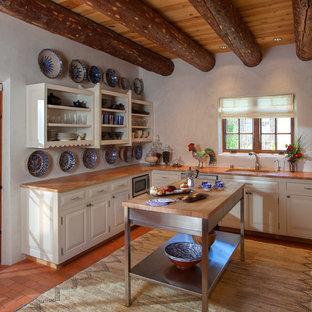 Inspiration pour une cuisine américaine sud-ouest américain avec un évier posé, un placard à porte plane, des portes de placard blanches, un plan de travail en bois, un électroménager en acier inoxydable, un sol en brique et un îlot central.