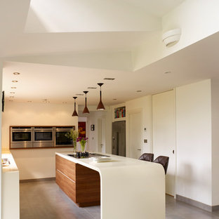 Kitchen - mid-sized contemporary l-shaped kitchen idea in Manchester with stainless steel appliances, flat-panel cabinets, white cabinets and an island