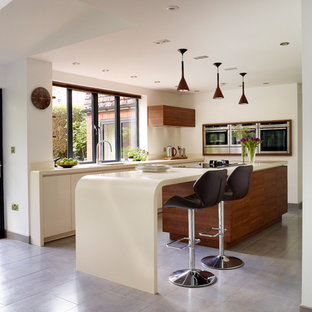 Inspiration for a mid-sized contemporary l-shaped kitchen remodel in Manchester with an undermount sink, flat-panel cabinets, white cabinets, stainless steel appliances and an island