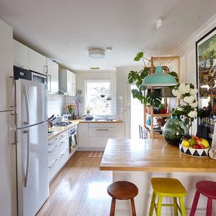 Inspiration for an eclectic kitchen in Melbourne with flat-panel cabinets, white cabinets, wood benchtops, white splashback, subway tile splashback, white appliances and medium hardwood floors.