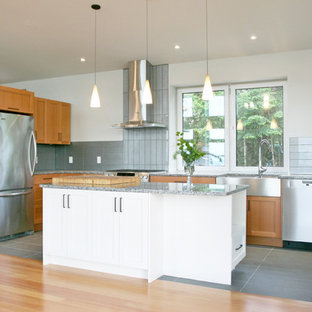 Design ideas for a mid-sized contemporary l-shaped eat-in kitchen in Vancouver with a farmhouse sink, shaker cabinets, medium wood cabinets, granite benchtops, grey splashback, glass tile splashback, stainless steel appliances, cement tiles, with island and grey floor.