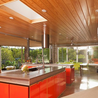 Photo of a midcentury eat-in kitchen in Tampa with an undermount sink, concrete benchtops, stainless steel appliances, flat-panel cabinets and red cabinets.