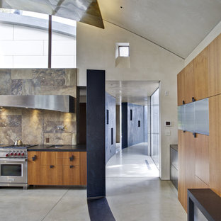 Large trendy l-shaped concrete floor open concept kitchen photo in San Francisco with stainless steel appliances, flat-panel cabinets, medium tone wood cabinets, brown backsplash, an undermount sink, soapstone countertops, slate backsplash and an island