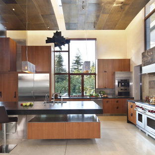 This is an example of a large contemporary l-shaped open plan kitchen in San Francisco with stainless steel appliances, flat-panel cabinets, medium wood cabinets, soapstone benchtops, brown splashback, an undermount sink, slate splashback, concrete floors and with island.