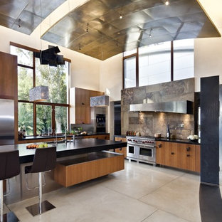 Inspiration for a large contemporary l-shaped open plan kitchen in San Francisco with flat-panel cabinets, medium wood cabinets, soapstone benchtops, brown splashback, stainless steel appliances, slate splashback, an undermount sink, concrete floors, with island and grey floor.
