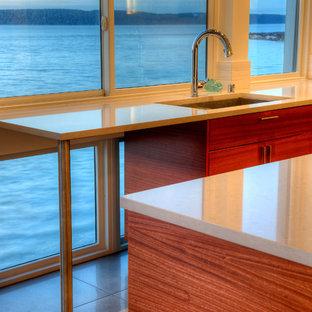 シアトルの中サイズのモダンスタイルのおしゃれなキッチン (アンダーカウンターシンク、フラットパネル扉のキャビネット、茶色いキャビネット、人工大理石カウンター、白いキッチンパネル、ガラスまたは窓のキッチンパネル、シルバーの調理設備、磁器タイルの床、ベージュの床、白いキッチンカウンター) の写真