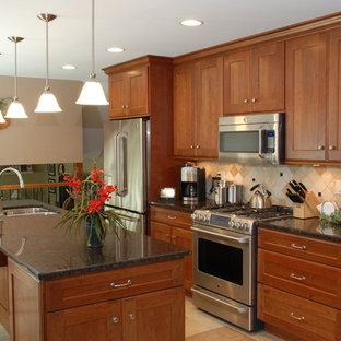 シカゴの中サイズのサンタフェスタイルのおしゃれなキッチン (アンダーカウンターシンク、フラットパネル扉のキャビネット、中間色木目調キャビネット、御影石カウンター、シルバーの調理設備の) の写真