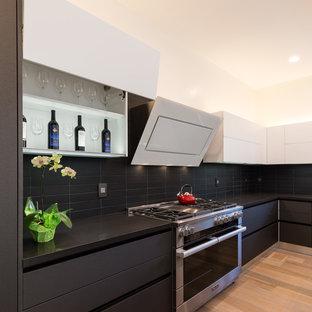 サンフランシスコの大きいモダンスタイルのおしゃれなキッチン (アンダーカウンターシンク、フラットパネル扉のキャビネット、黒いキャビネット、クオーツストーンカウンター、黒いキッチンパネル、セラミックタイルのキッチンパネル、シルバーの調理設備、無垢フローリング、茶色い床、黒いキッチンカウンター) の写真