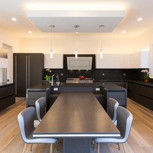 Foto di una grande cucina abitabile minimalista con lavello sottopiano, ante lisce, ante nere, top in quarzo composito, paraspruzzi nero, paraspruzzi con piastrelle in ceramica, elettrodomestici in acciaio inossidabile, isola, top nero, parquet chiaro e pavimento beige