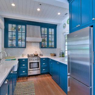 Bild på ett avskilt, litet maritimt u-kök, med en rustik diskho, blå skåp, vitt stänkskydd, rostfria vitvaror, mellanmörkt trägolv, luckor med glaspanel och stänkskydd i stickkakel
