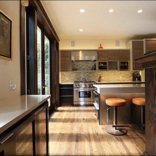 ポートランドの広いエクレクティックスタイルのおしゃれなキッチン (アンダーカウンターシンク、フラットパネル扉のキャビネット、淡色木目調キャビネット、クオーツストーンカウンター、黄色いキッチンパネル、ガラスタイルのキッチンパネル、シルバーの調理設備、濃色無垢フローリング) の写真