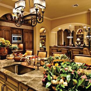 マイアミの巨大な地中海スタイルのおしゃれなキッチン (アンダーカウンターシンク、落し込みパネル扉のキャビネット、中間色木目調キャビネット、御影石カウンター、ベージュキッチンパネル、石タイルのキッチンパネル、パネルと同色の調理設備、トラバーチンの床) の写真