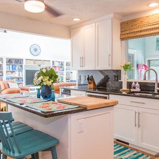 Große Shabby-Look Wohnküche in L-Form mit Doppelwaschbecken, Schrankfronten im Shaker-Stil, weißen Schränken, Granit-Arbeitsplatte, Küchenrückwand in Schwarz, Rückwand aus Stein, Küchengeräten aus Edelstahl, braunem Holzboden, Kücheninsel und braunem Boden in Sonstige