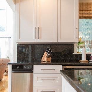 他の地域の大きいシャビーシック調のおしゃれなキッチン (ダブルシンク、シェーカースタイル扉のキャビネット、白いキャビネット、御影石カウンター、黒いキッチンパネル、石スラブのキッチンパネル、シルバーの調理設備の、無垢フローリング、茶色い床) の写真