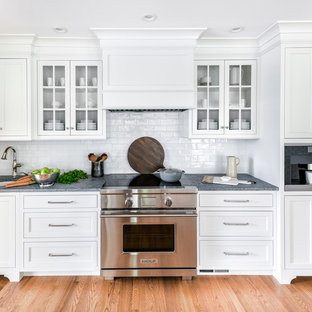 Large transitional eat-in kitchen designs - Example of a large transitional l-shaped light wood floor eat-in kitchen design in Philadelphia with a farmhouse sink, flat-panel cabinets, white cabinets, soapstone countertops, white backsplash, ceramic backsplash, paneled appliances, an island and gray countertops