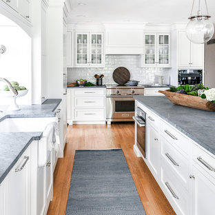This is an example of a large transitional u-shaped kitchen in Philadelphia with a farmhouse sink, white cabinets, soapstone benchtops, white splashback, ceramic splashback, panelled appliances, with island, grey benchtop, shaker cabinets, medium hardwood floors and brown floor.