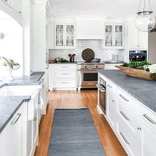フィラデルフィアの大きいトランジショナルスタイルのおしゃれなキッチン (エプロンフロントシンク、白いキャビネット、ソープストーンカウンター、白いキッチンパネル、セラミックタイルのキッチンパネル、パネルと同色の調理設備、グレーのキッチンカウンター、シェーカースタイル扉のキャビネット、無垢フローリング、茶色い床) の写真