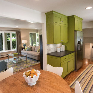 Small midcentury galley open plan kitchen in Grand Rapids with an undermount sink, shaker cabinets, green cabinets, laminate benchtops, white splashback, stone tile splashback, stainless steel appliances, medium hardwood floors and no island.