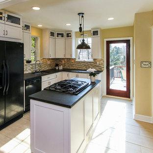 Klassisk inredning av ett mellanstort svart svart kök, med en undermonterad diskho, luckor med infälld panel, vita skåp, bänkskiva i koppar, flerfärgad stänkskydd, stänkskydd i glaskakel, svarta vitvaror, klinkergolv i porslin, en köksö och beiget golv