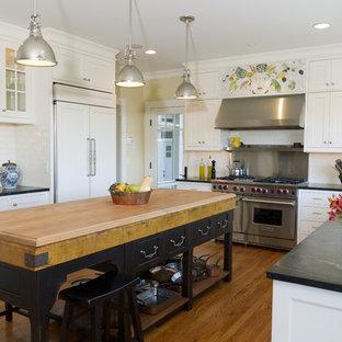 Inspiration för mellanstora klassiska svart kök, med luckor med infälld panel, integrerade vitvaror, bänkskiva i täljsten, vita skåp, en undermonterad diskho, vitt stänkskydd, stänkskydd i keramik, mellanmörkt trägolv, brunt golv och en köksö
