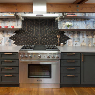 Diseño de cocina bohemia con armarios estilo shaker, puertas de armario grises, salpicadero multicolor, electrodomésticos de acero inoxidable, suelo de madera en tonos medios y suelo marrón