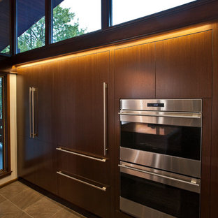 This is an example of a large midcentury galley eat-in kitchen in Cincinnati with a single-bowl sink, flat-panel cabinets, medium wood cabinets, quartz benchtops, stainless steel appliances, porcelain floors and with island.