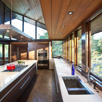 Inspiration for a large mid-century modern galley porcelain tile eat-in kitchen remodel in Cincinnati with a single-bowl sink, flat-panel cabinets, medium tone wood cabinets, quartz countertops, stainless steel appliances and an island
