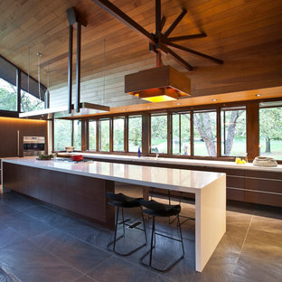 Inspiration for a large midcentury galley eat-in kitchen in Cincinnati with a single-bowl sink, flat-panel cabinets, medium wood cabinets, quartz benchtops, stainless steel appliances, porcelain floors and with island.