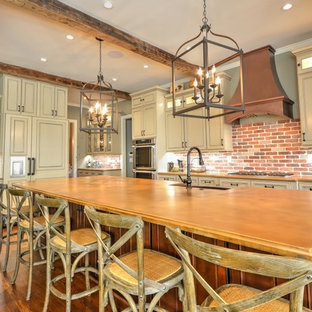 Kitchen pictures - Dark wood floor kitchen photo in Atlanta with a farmhouse sink, raised-panel cabinets, concrete countertops, brick backsplash, stainless steel appliances and an island