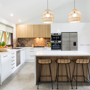 This is an example of a contemporary l-shaped kitchen in Other with a drop-in sink, flat-panel cabinets, white cabinets, brown splashback, brick splashback, stainless steel appliances, concrete floors, a peninsula, grey floor and white benchtop.