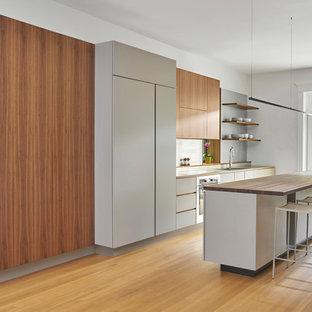シカゴのモダンスタイルのおしゃれなキッチン (フラットパネル扉のキャビネット、グレーのキャビネット、木材カウンター、パネルと同色の調理設備、茶色い床、無垢フローリング、茶色いキッチンカウンター) の写真