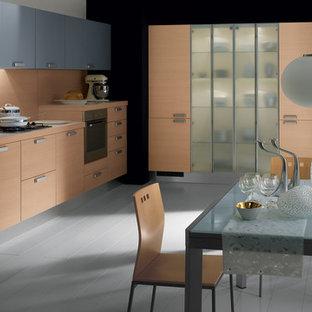 Immagine di una grande cucina moderna con lavello a doppia vasca, ante con bugna sagomata, ante in legno chiaro, top in quarzo composito, elettrodomestici neri, pavimento in legno verniciato e 2 o più isole
