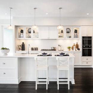 Idéer för att renovera ett stort funkis vit vitt kök, med en dubbel diskho, skåp i shakerstil, vita skåp, bänkskiva i kvarts, vitt stänkskydd, stänkskydd i tunnelbanekakel, rostfria vitvaror, mörkt trägolv, en köksö och svart golv